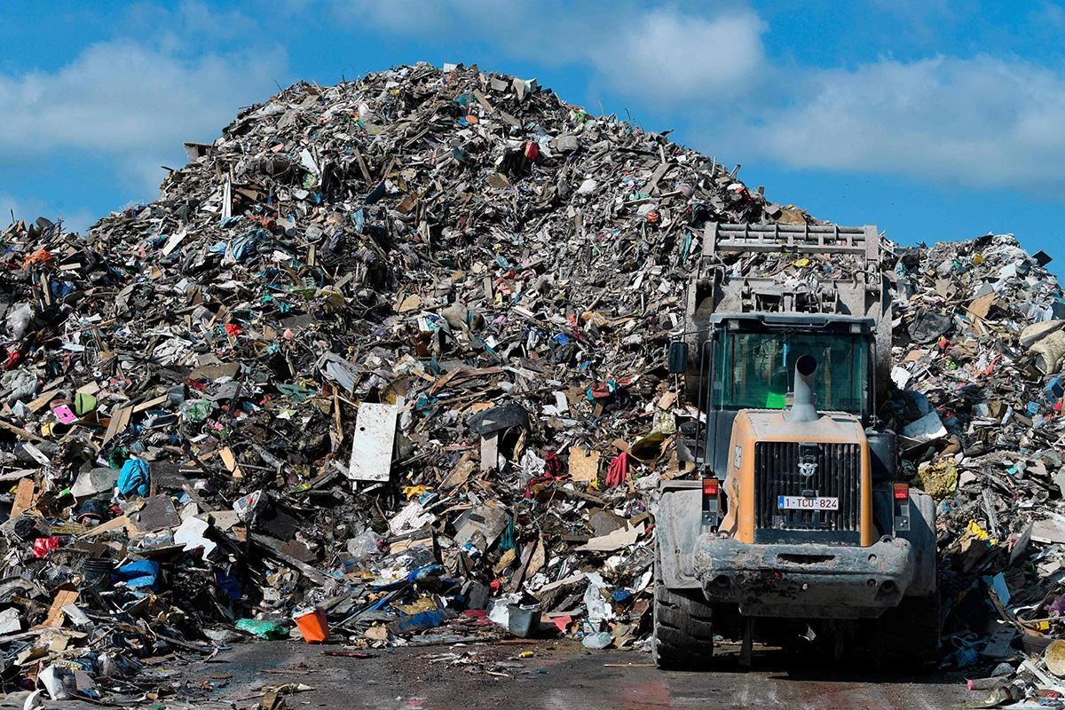 Sekalaista tulvajätettä on läjitetty tilapäisiin säilytyspaikkoihin. Kauhakuormaaja kasasi jätteitä Belgian Rochefortissa 19. heinäkuuta.