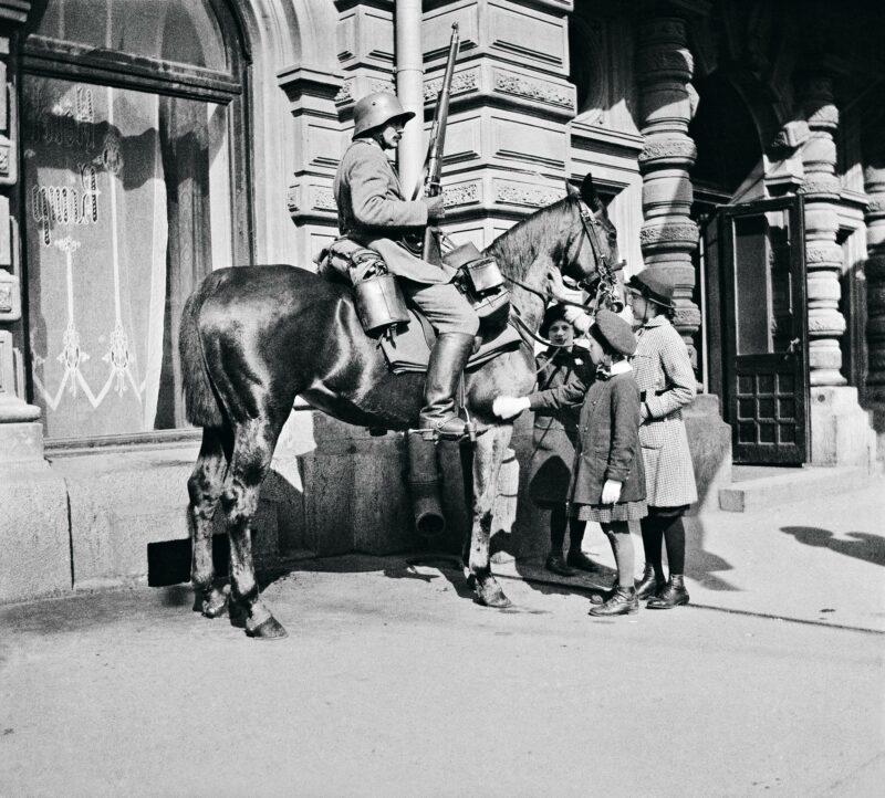 Helsinkiläislapset tutustuvat saksalaisen vartiosotilaan hevoseen hotelli Kämpin edustalla vuonna 1918. Kämp toimi saksalaisjoukkojen päämajana.