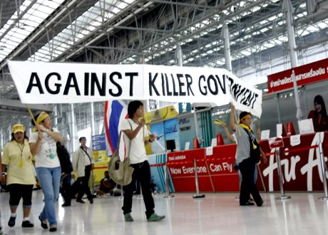Student protesters hold a banner past Air Asia counter during a protest at Suvarnabhumi airport Wednesday, Nov. 26, 2008, in Bangkok, Thailand. The protest have forced the cancellation of outgoing and incoming of both domestic and international flights and stranding thousands of tourists when protesters demand the immediately resignation of the government of Prime Minister Somchai Wongsawat. (AP Photo/Apichart Weerawong)