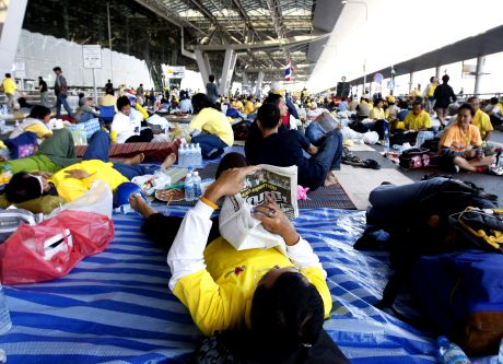Anti-government protesters read a newspaper at Suvarnabhumi airport, Bangkok's main international airport, on Thursday, Nov. 27, 2008, in Bangkok, Thailand. Thai authorities shut down Bangkok's second airport Thursday after it was overrun by anti-government protesters, completely cutting off the capital from air traffic as the prime minister rejected their demands to resign, deepening the country's crisis.(AP Photo/Vincent Thian)