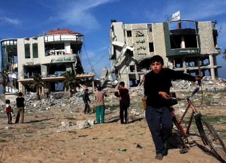 "Palestinian children gather around the remains of the Jazeera hotel destroyed in Israeli military operations in Gaza City, Tuesday, Jan. 13, 2009. Israeli troops advanced into Gaza suburbs for the first time early Tuesday, residents said, hours after Prime Minister Ehud Olmert warned Islamic militants that they face an ""iron fist"" unless they agree to Israeli terms for an end to war in the Gaza Strip. (AP Photo/Khalil Hamra)"