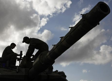 Israeli soldiers stand on top of a tank at a staging area on the Israel-Gaza border, Saturday, Jan. 17, 2009. Israel's leaders voted late Saturday to halt an offensive that has killed nearly 1,200 people, turned the streets and neighborhoods of the Gaza Strip into battlegrounds and dealt a stinging blow to the Islamic militants of Hamas. (AP Photo/Tsafrir Abayov)