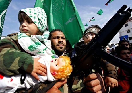 A Hamas militant and his two children participate in a rally in Palestine Square in Gaza City, in the northern Gaza strip, Tuesday, Jan. 20, 2009. U.N. chief Ban Ki-moon inspected the devastation wrought by Israel's onslaught in Gaza on Tuesday, leading a moment of silence at the U.N. headquarters, as the territory's militant Hamas rulers, triumphant at having survived, held victory rallies amid the ruins. (AP Photo/Ben Curtis)