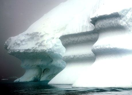 An iceberg melts in circular patterns in Kulusuk Bay, eastern Greenland, Tuesday July 17, 2007. The melting of the Greenland ice cap and its effect on the the area around Greenland is one of the more immediate effects of climate change. (AP Photo/John McConnico)