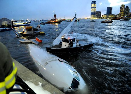 A US Airways plane rests against a retaining wall after the pilot ditched the disabled jetliner into the frigid Hudson River in New York Thursday, Jan. 15, 2009. A collision with a flock of birds apparently knocked out both engines, but rescuers pulled all 155 people on board into boats as the plane sank. (AP Photo/Louis Lanzano)