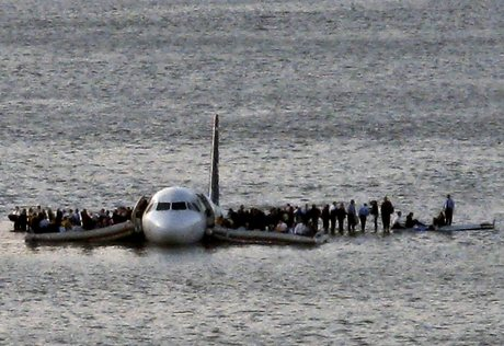 Airline passengers wait to board a ferry to be rescued on the wings of a US Airways Airbus 320 jetliner that safely ditched in the frigid waters of the Hudson River in New York, Thursday Jan. 15, 2009 after a flock of birds knocked out both its engines. All 155 people on board survived. (AP Photo/Steven Day)