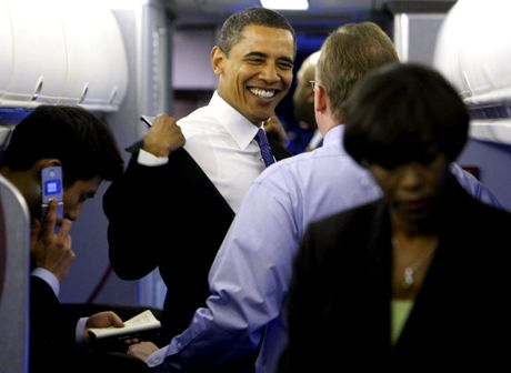 President-elect Obama takes off his jacket as he talks with adviser Robert Gibbs after boarding his plane at Washington's Reagan National Airport after meeting with President Bush at the White House in Washington, Monday, Nov. 10, 2008. (AP Photo/Charles Dharapak)