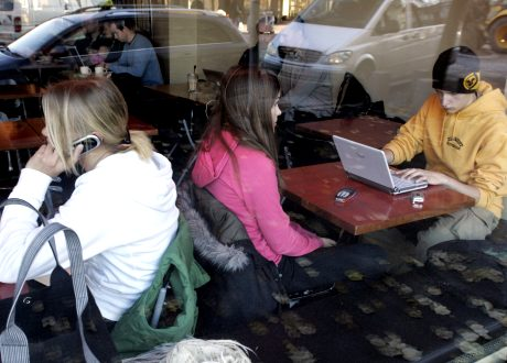 Nuori nainen puhuu matkapuhelimeen ja nuori mies surffailee Internetissä nettikahvilassa Helsingissä. Kannettava tietokone.